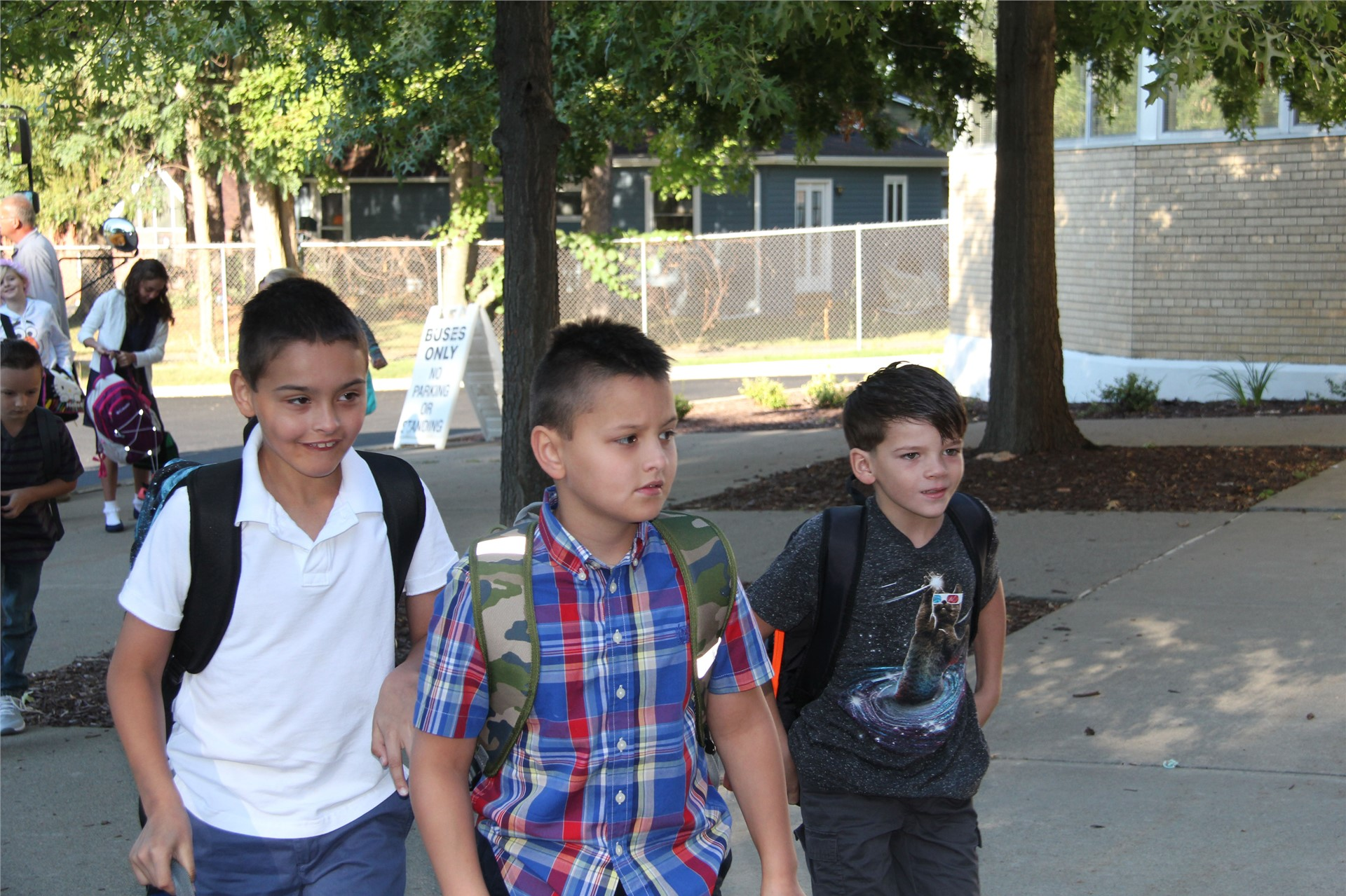 three students walking towards school