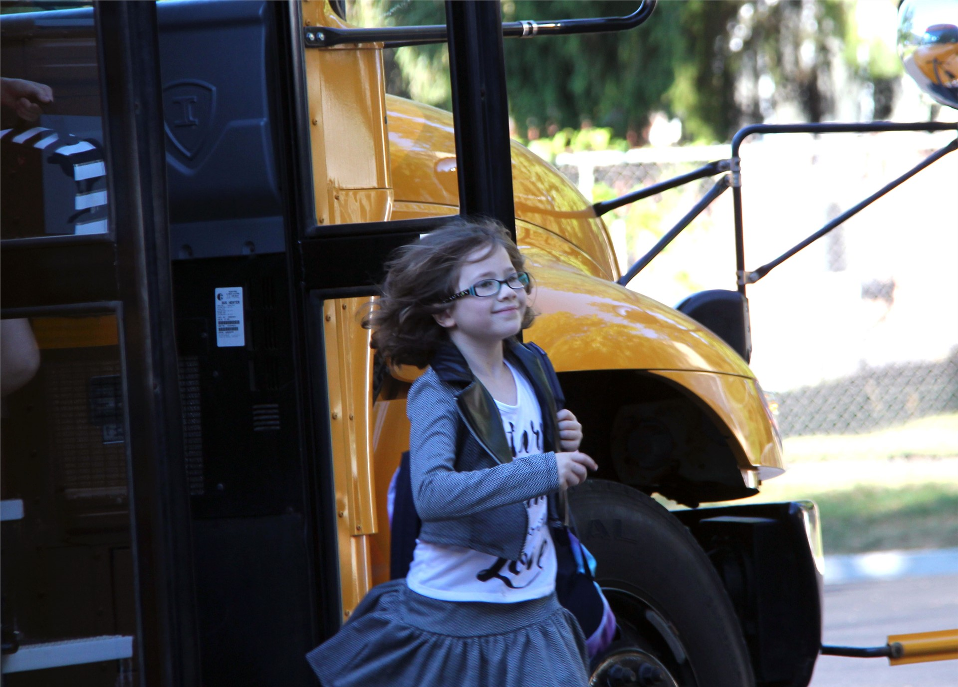 student smiling exiting school bus