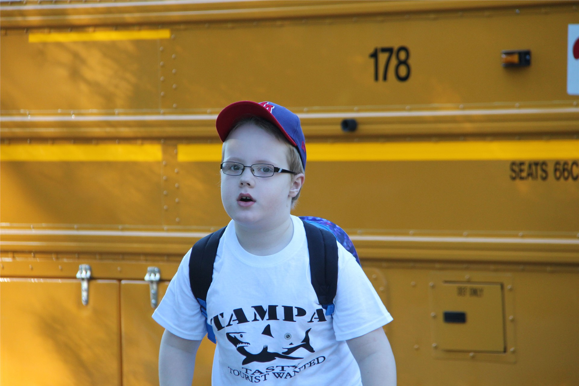 student standing by bus