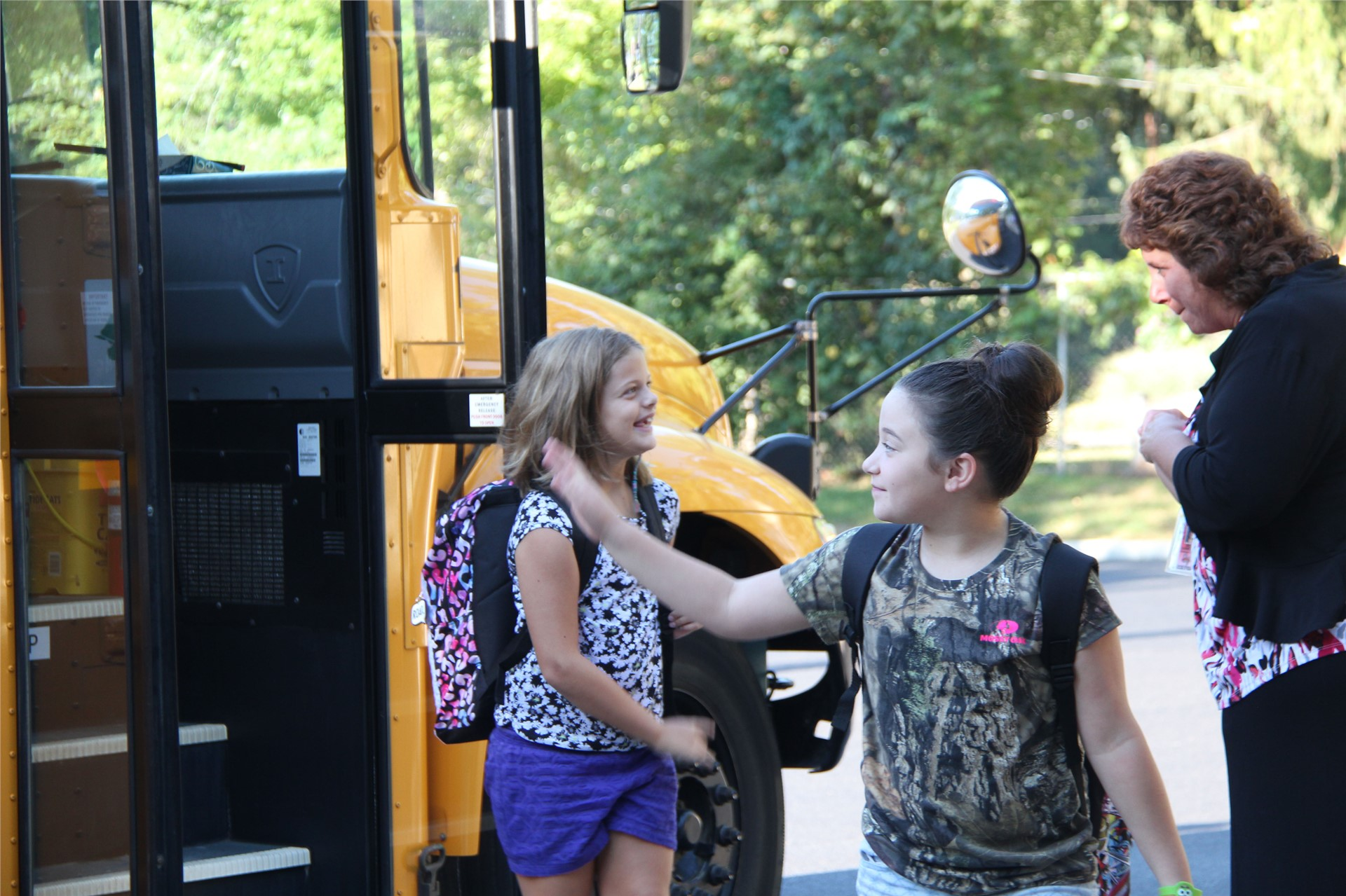 principal hammond greeting students off bus