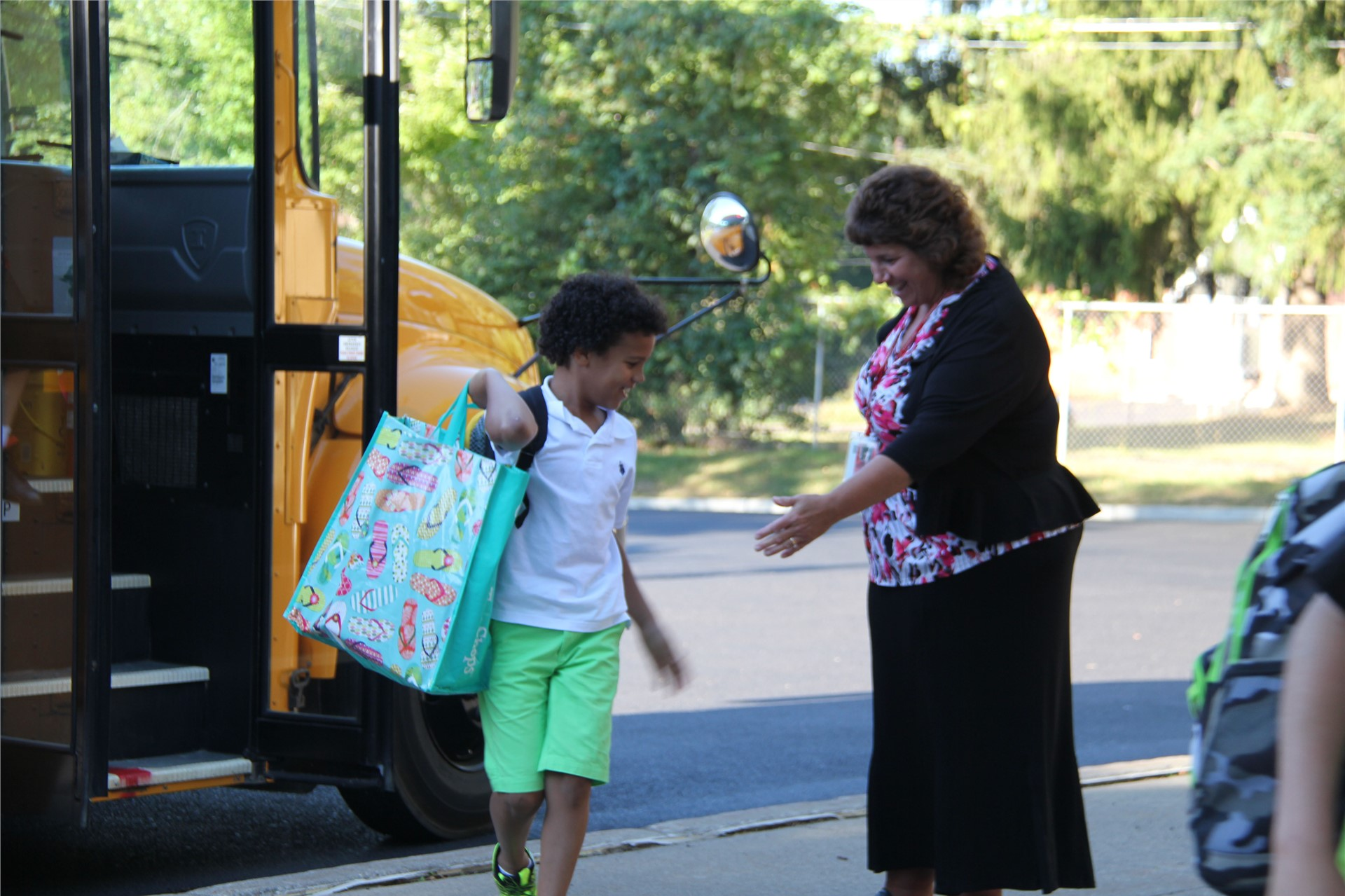 principal hammond greeting student off bus