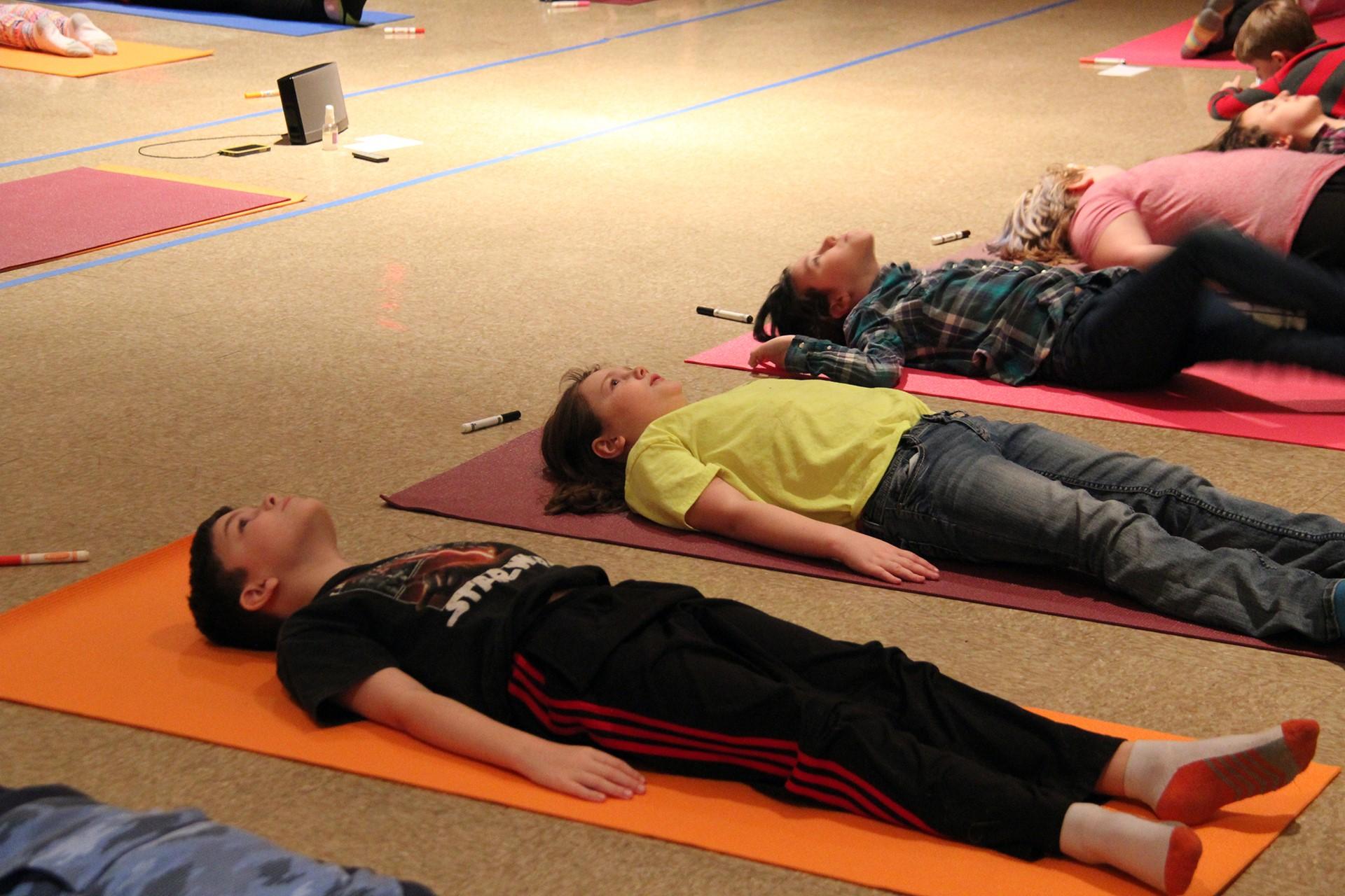 students laying on yoga mats