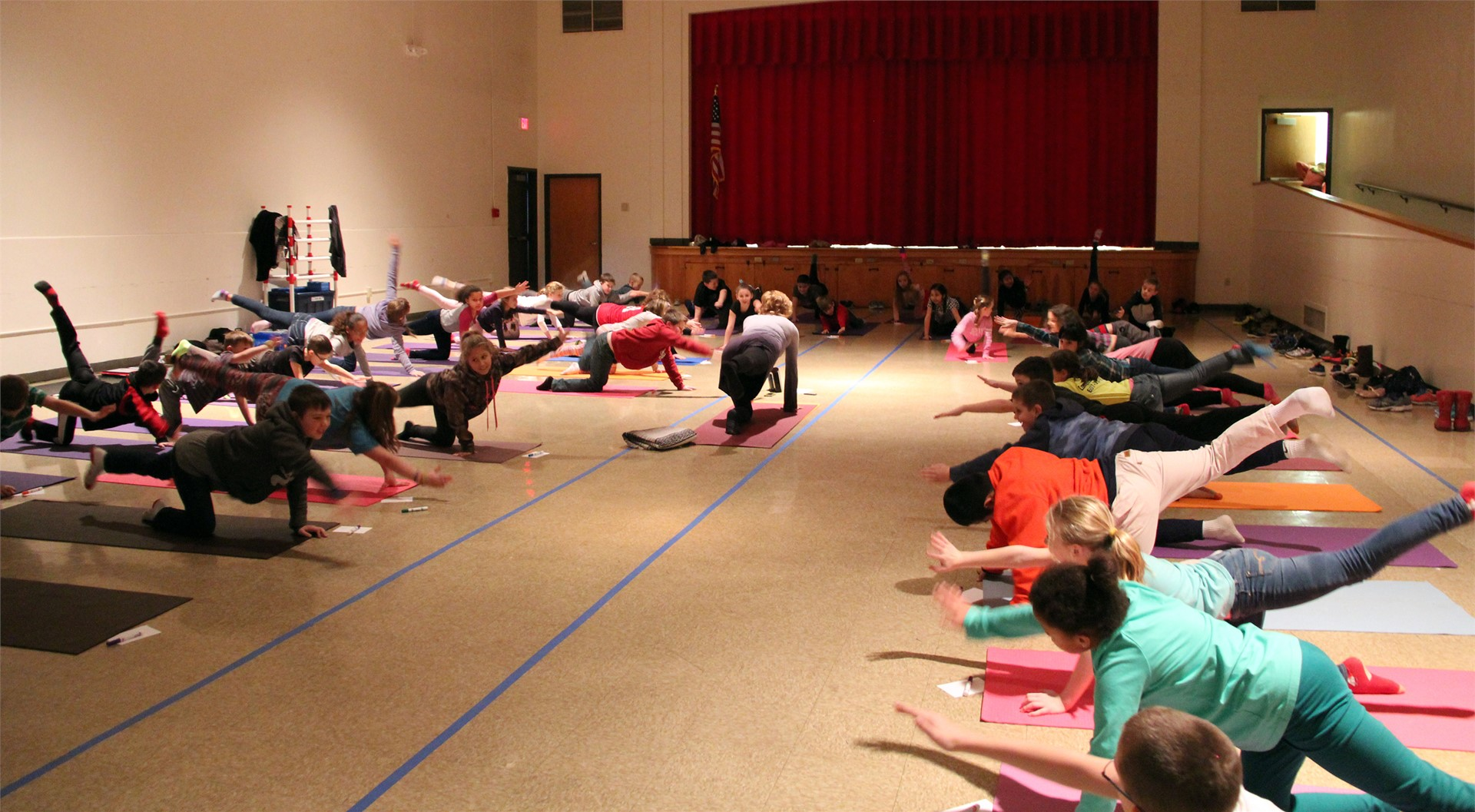 students learning yoga in auditorium