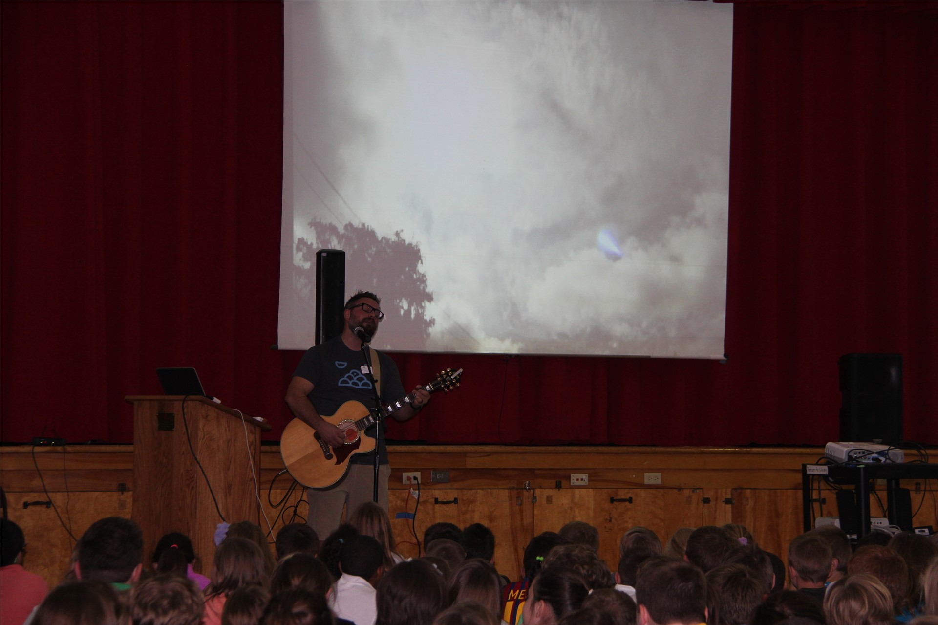 jared campbell singing in front of screen wide shot