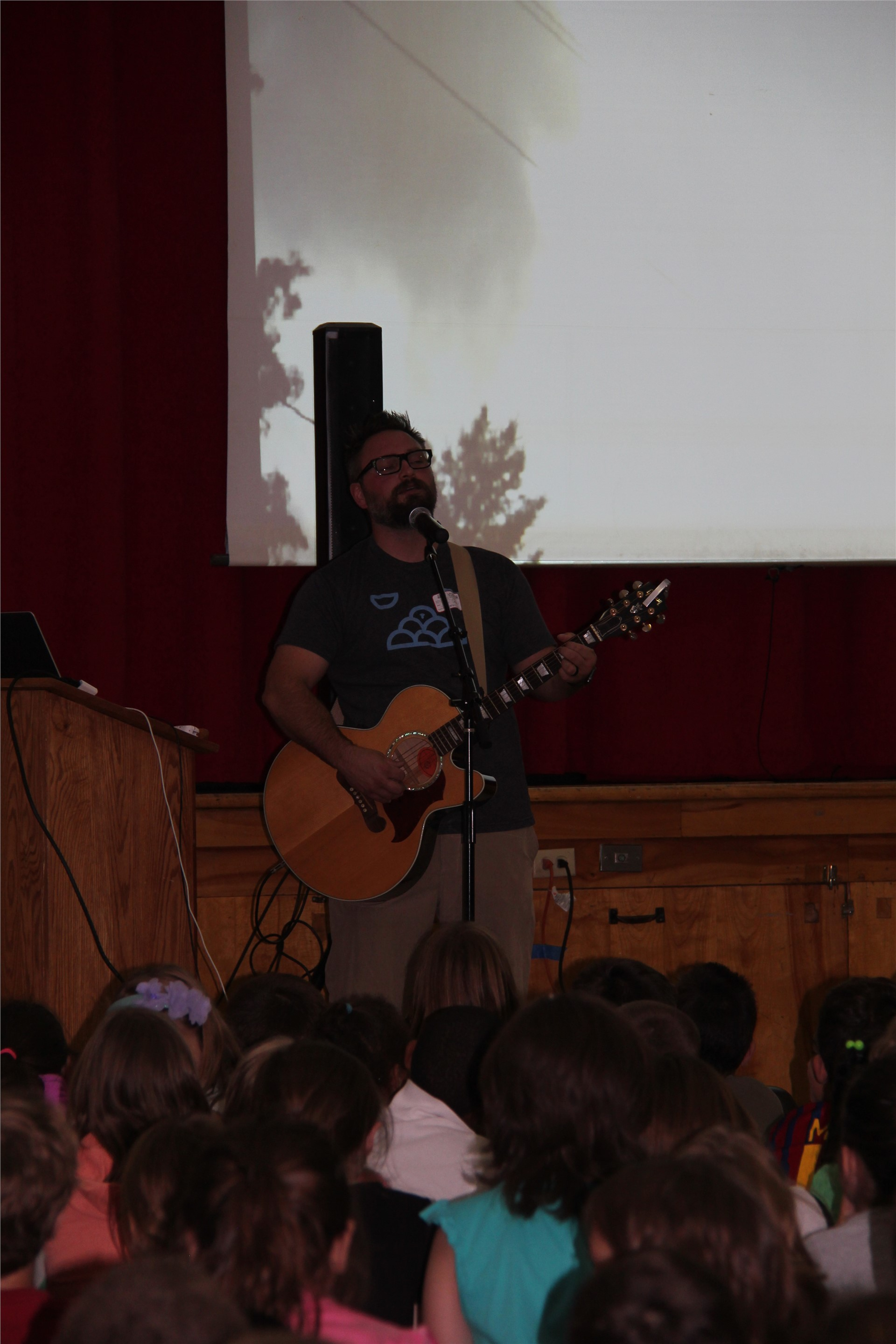 medium shot of jared campbell performing in front of screen