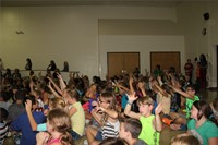 students with hands in air listening to music