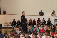 Officer talking to students in auditorium