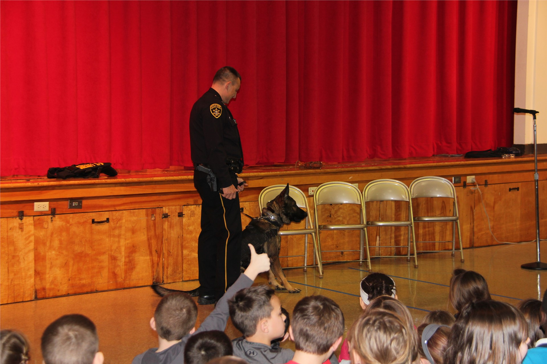 officer with dog in front of students