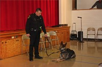 officer standing with police dog laying down