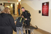 student petting police dog