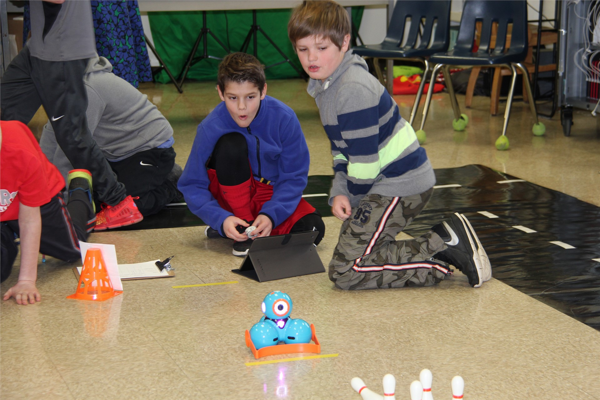 students watch electronic device on floor