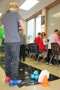 students work with electronic device on course