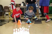 students set up electronic device by bowling pins