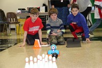 students watch electronic device move towards bowling pins