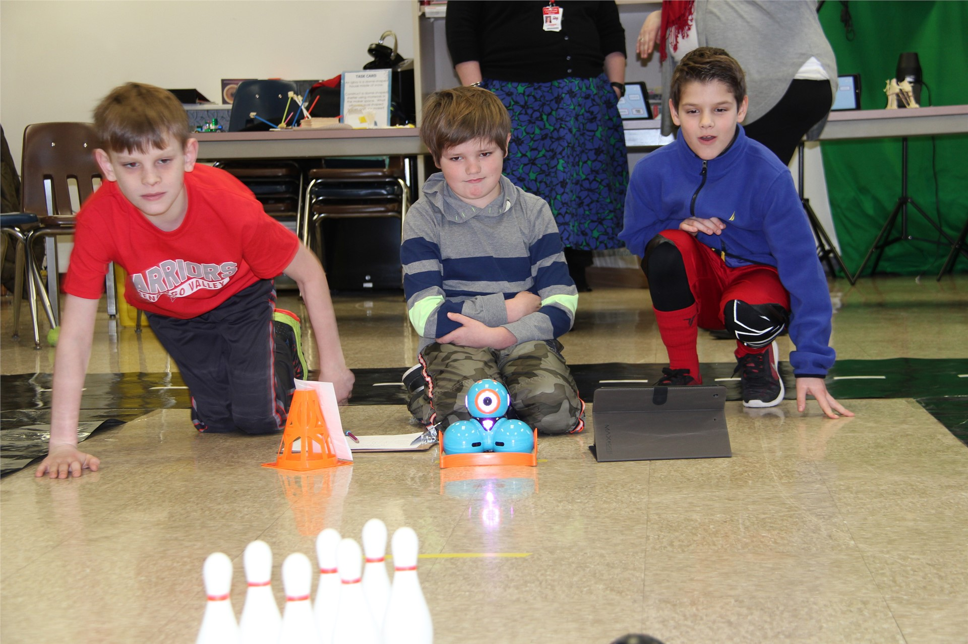 students play with electronic device and bowling pins