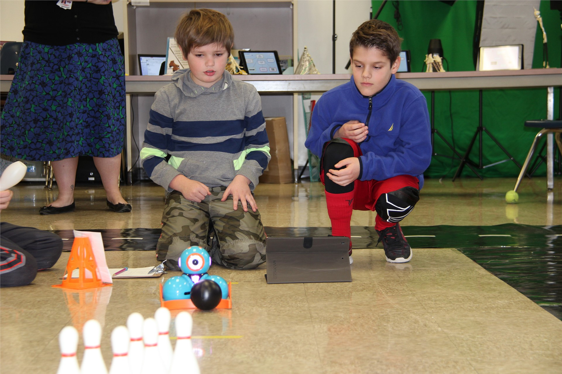 two students watch electronic device move towards bowling pins