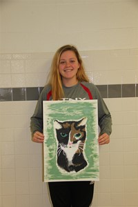 student holding painting of cat