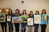 group of students holding illustrations of animals
