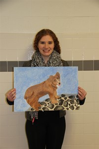 student holding painting of dog