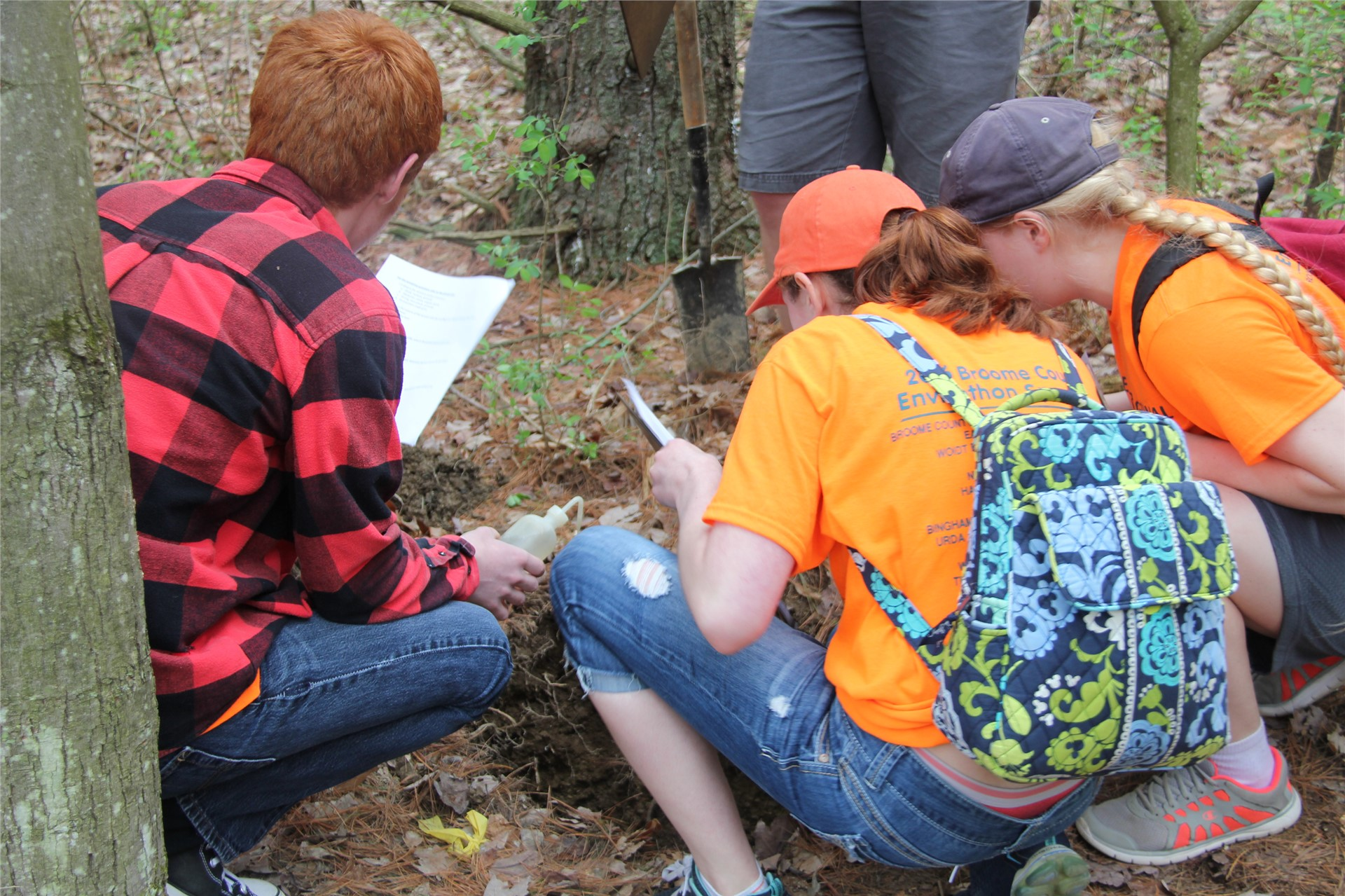 students looking at object in wooded area