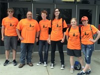 group of students standing in orange t shirts