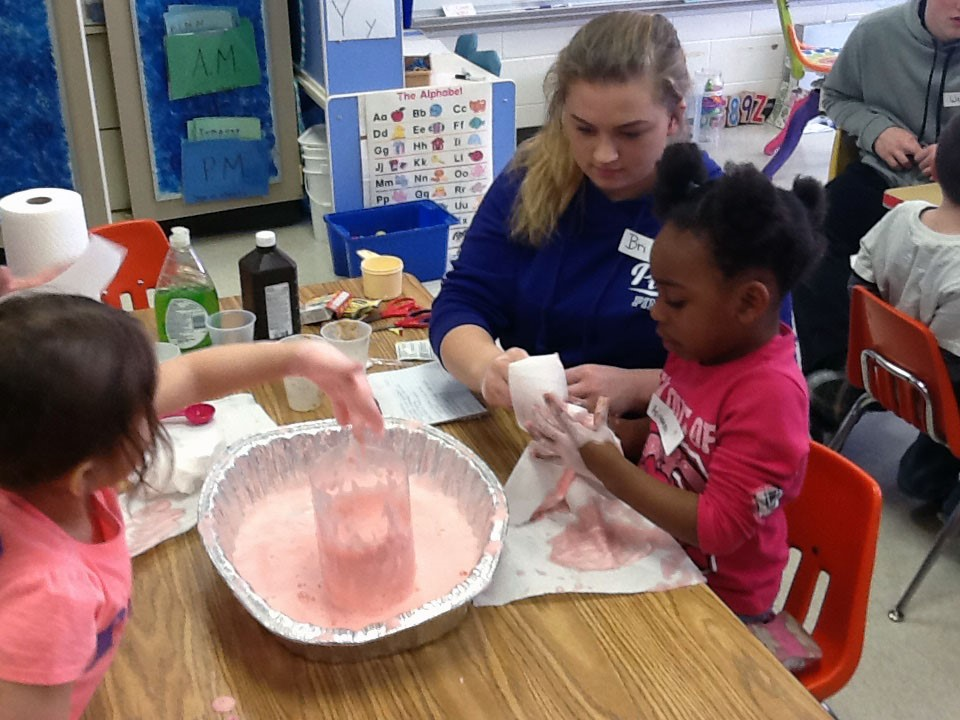 chemistry students works at table with pre k students