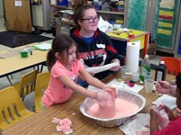 chemistry student works with pre k student