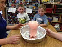close up of science project with pre k students looking at it