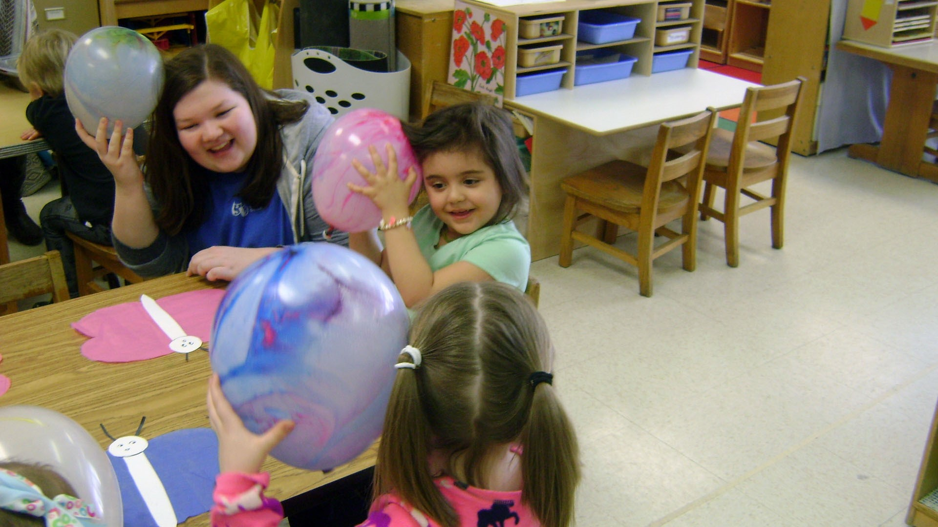 students rub balloons on hair for static electricity