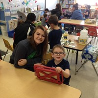 chemistry student and pre k student smile while sitting