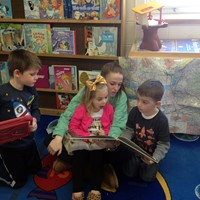 chemistry student reads book with pre k students
