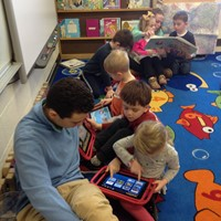 students sitting on rug looking at i pads