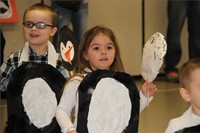 students smile walking wearing penguin costumes