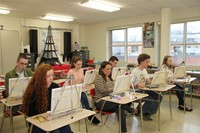 wide shot of people painting in classroom