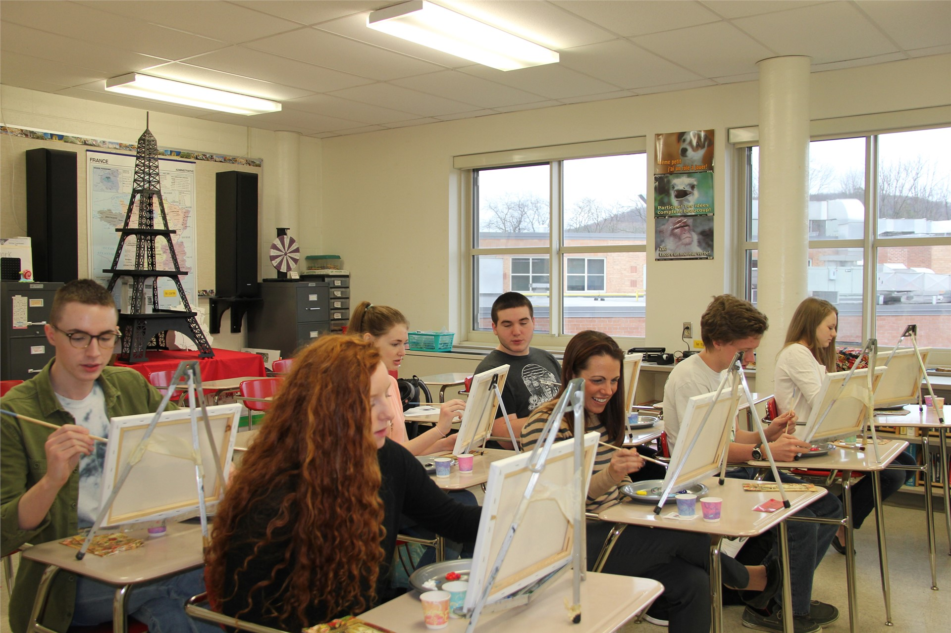 wide shot of students painting at desks