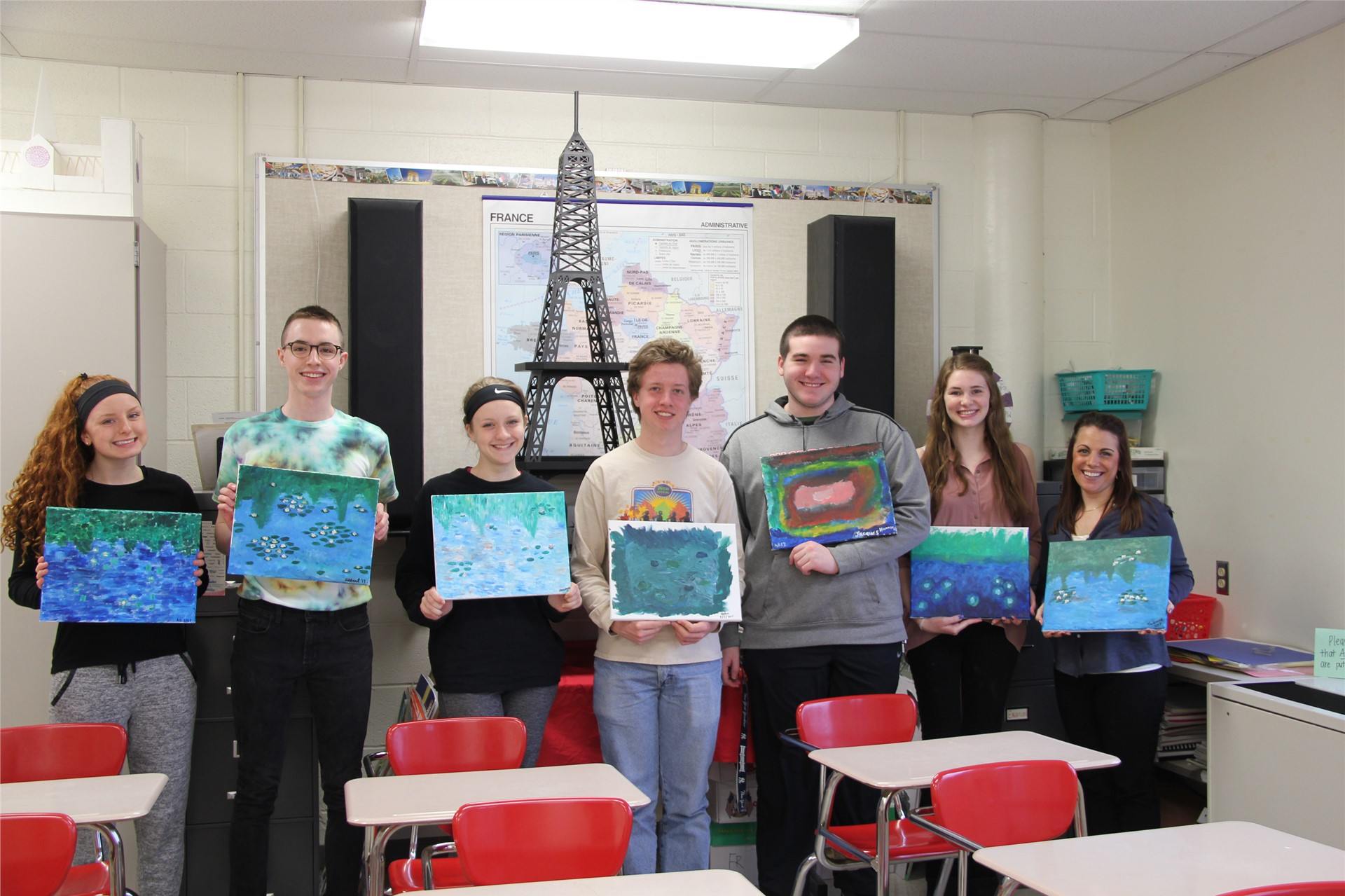 students and teacher holding their paintings