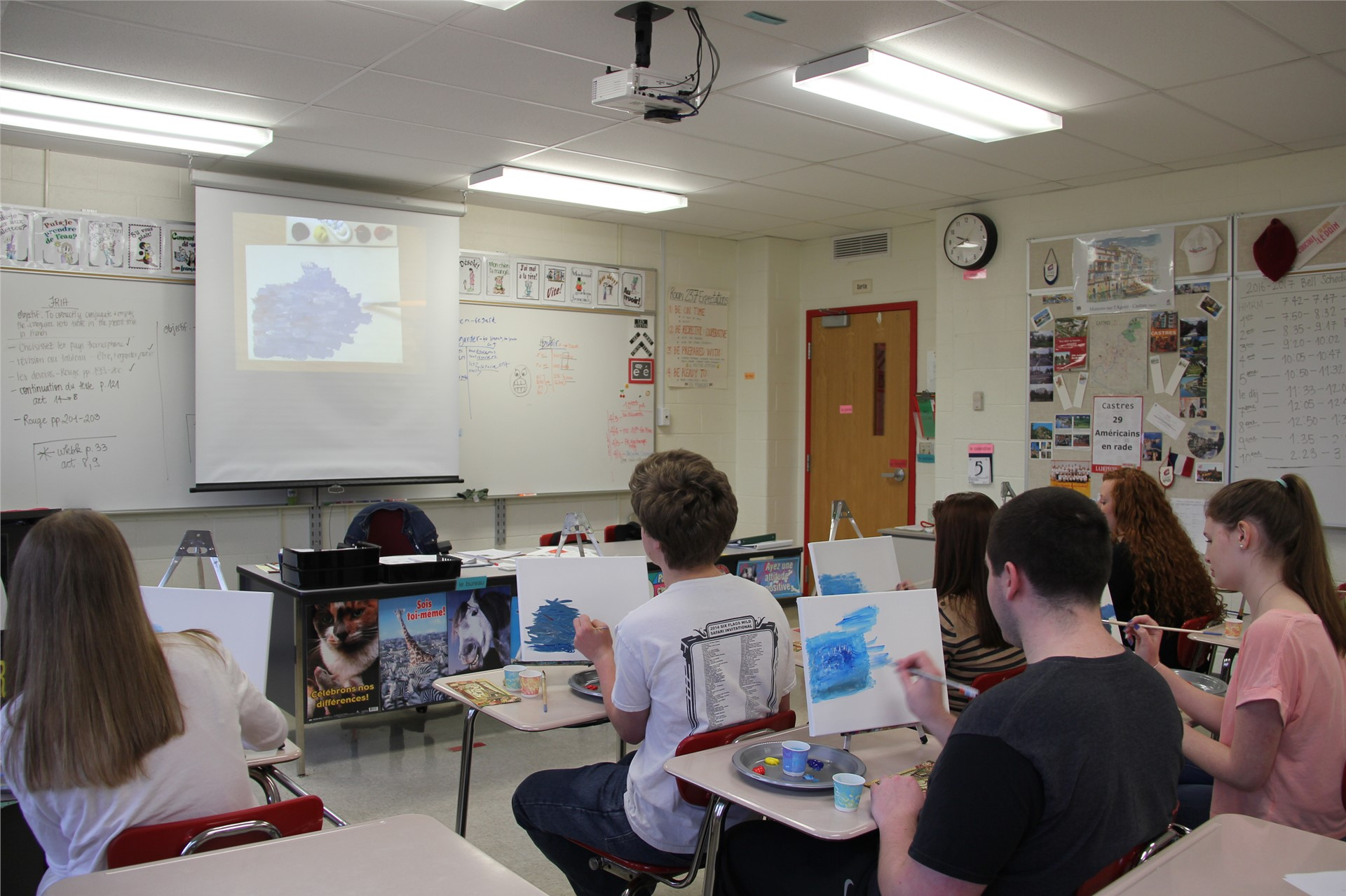 students painting a picture shown on screen