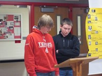 two students talking at podium
