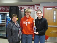 adult standing with two students with trophy