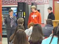 adult and two students standing while other student sit