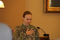 woman wearing military uniform standing with hand on heart