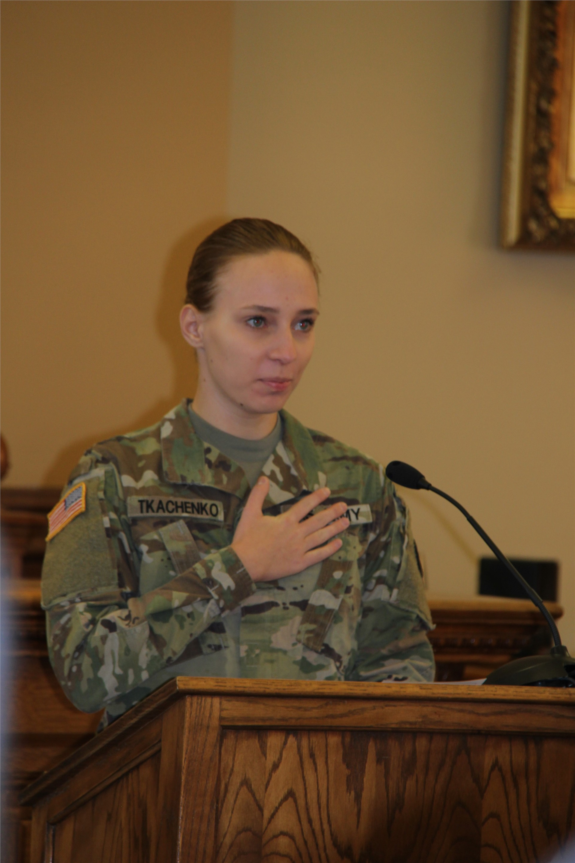 woman talking while wearing military uniform standing with hand on heart