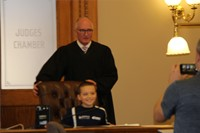 judge standing and child sitting in judges chair