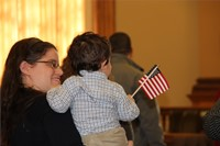 woman carrying child holding american flag