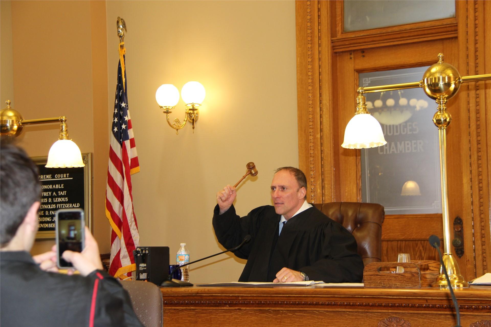 teacher sitting at judges chair holding gavel