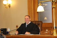 teacher sitting at judges chair smiling