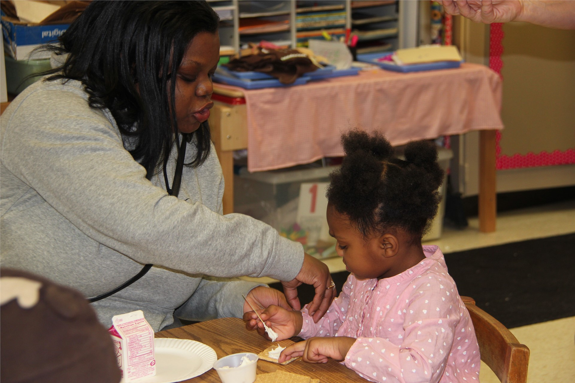 adult helping student decorate gingerbread cookie