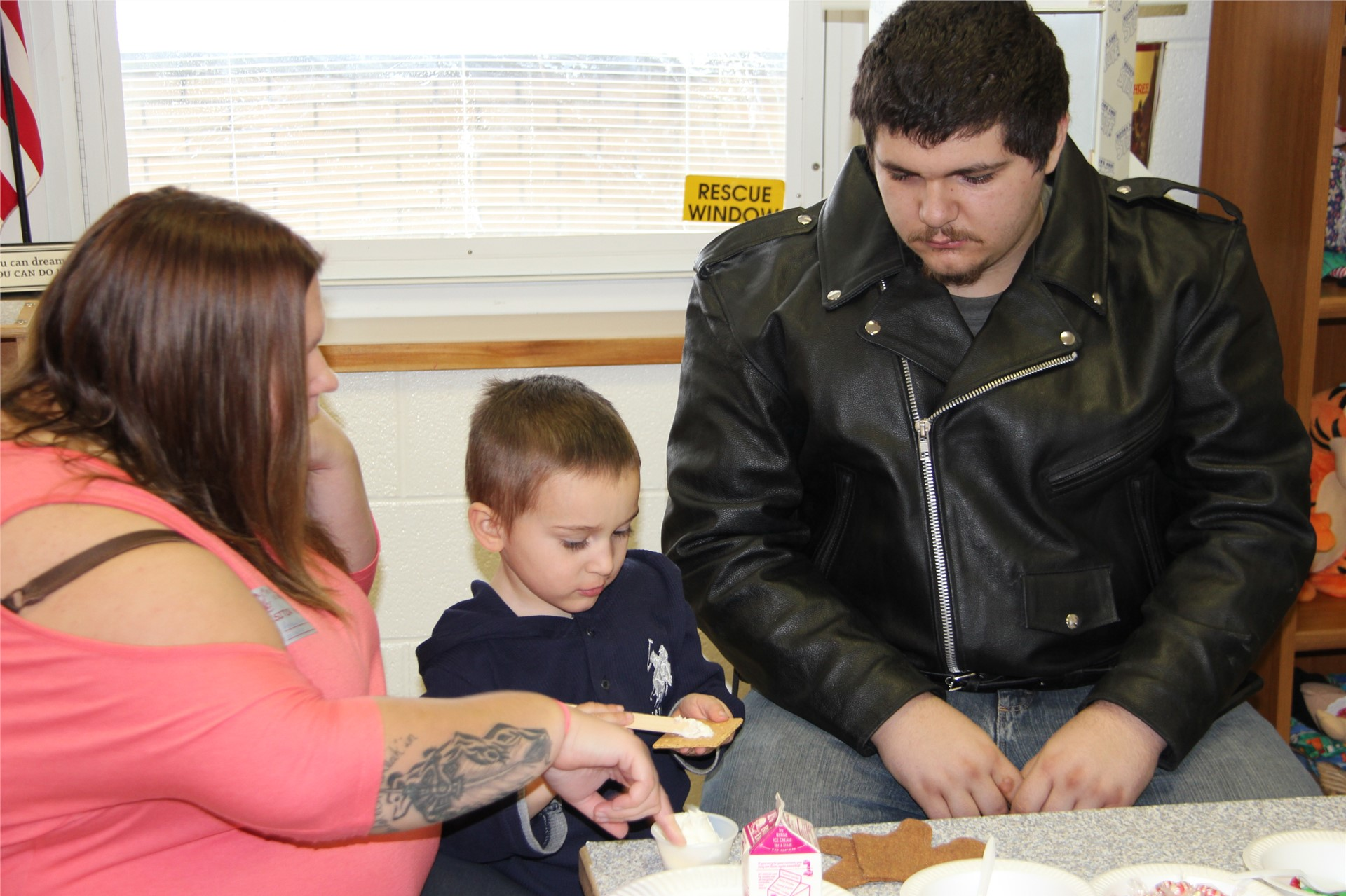 two adults helping student decorate gingerbread house