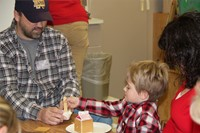 adult helping student decorate gingerbread house