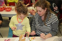 woman helping student decorate gingerbread house